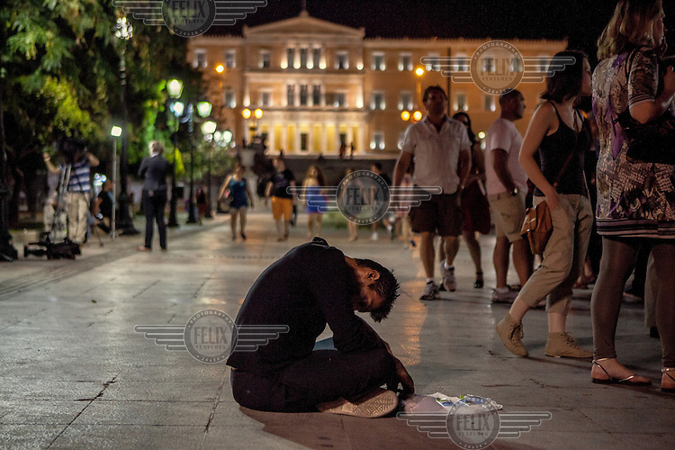 ATHENS; GREECE: a man apparently drunk or under the effects of narcotics sits in the middle of Syntagma square, in front of the Greek Parliament.