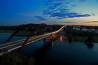 Night falls on the 360 Bridge as cars streak by in Austin, Texas