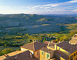 Tuscany, Italy      <br /> Colorful buildings and tiled roofs of Montepulciano with the rolling hills of the countryside in the background