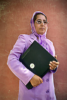 Farida, a deputy project manager for the NGO People in Need (PIN), stands holding a laptop.