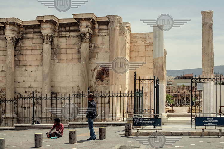 ATHENS, GREECE: a migrant begs close to Hadrian's Library, a touristic spot in the heart of the city.