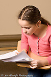 Elementary school Grade 5 arts enrichment female student singing notes from paper she holds vertical