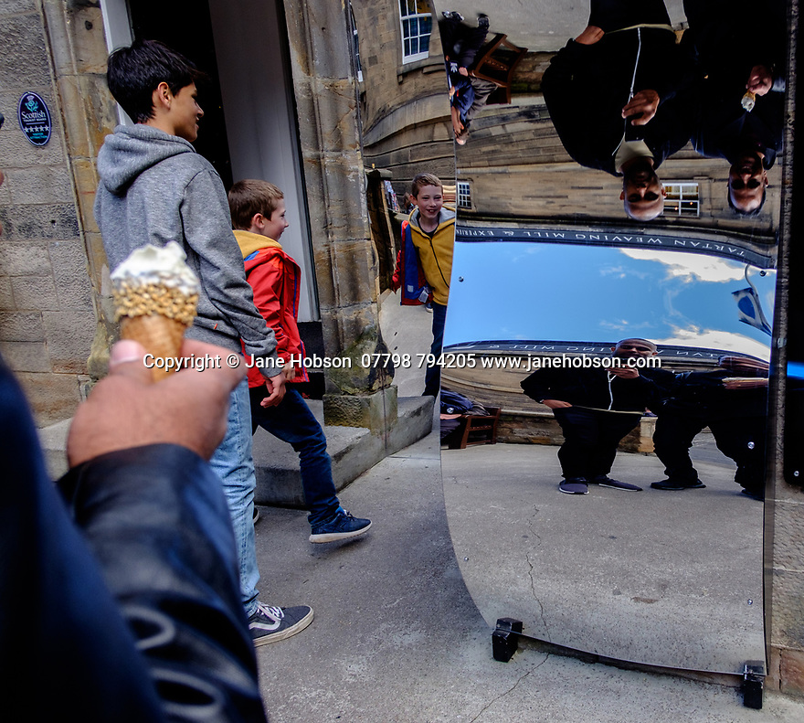 Edinburgh, UK. 15.04.2017. Visitors having fun with distorting mirrors outside the Camera Obscura, on the Royal Mile. Photograph © Jane Hobson.