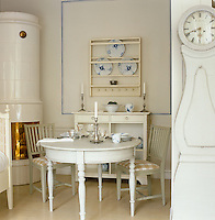 A traditional Swedish tiled stove and grandfather clock dominate this small contemporary dining room