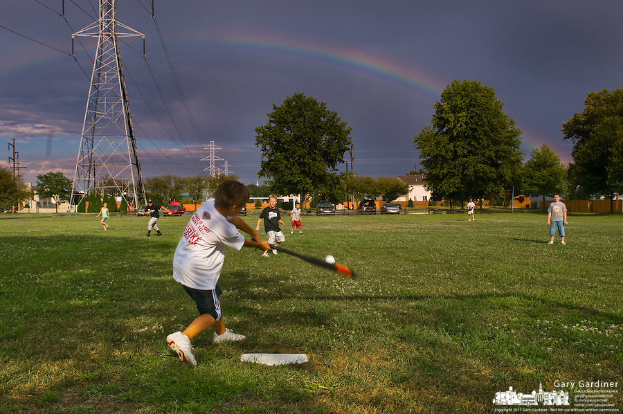 Children playing baseball at a picnic after a rain storm with rainbow filling darkened sky.