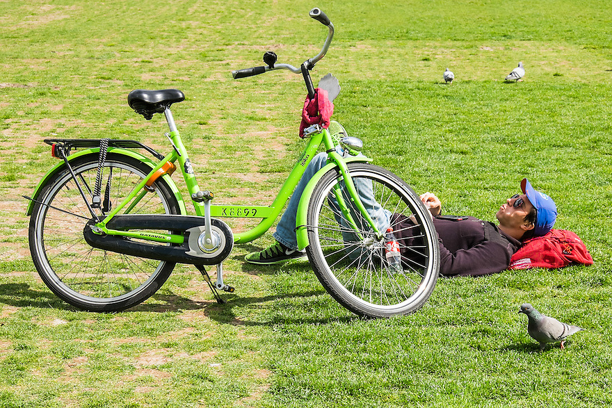 Nederland, Amsterdam, 30 mei 2015<br /> Museumplein. Man, toerist, ligt  in het gras van het Museumplein naast zijn huurfiets.  <br /> <br /> Foto: Michiel Wijnbergh