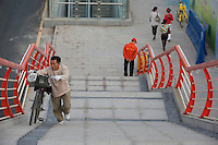 Daytime Landscape View Of A Man Pushing A Bicycle Up A Pedestrian Walkway Overpass in Guangzhou, China.  © LAN