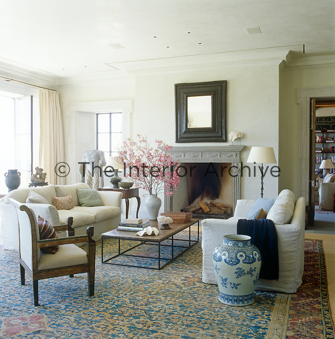 In the living room a neo-classical chair is paired with a vintage coffee table, custom-made linen-covered sofas and an antique Persian rug