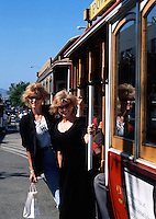 Women ride on a cable car as it travels on Market Street. San Francisco, California.