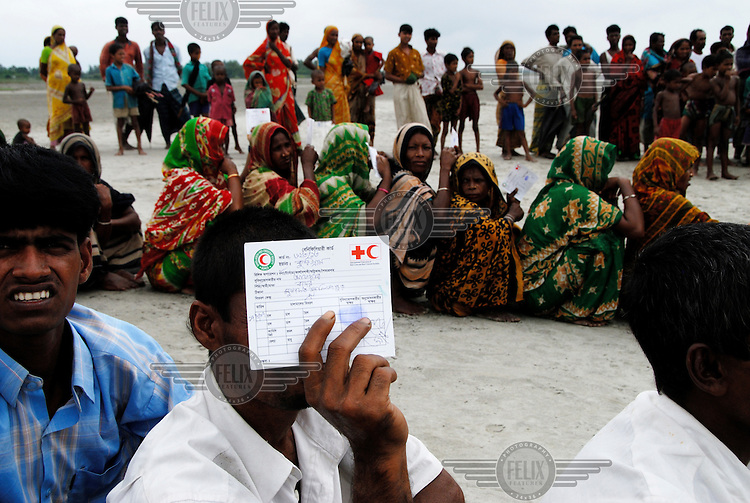 People wait for assistance with their Bangladesh Red Crescent Society aid cards after their village on the Oshdomi Chor (a small river island) was submerged by severe flooding.