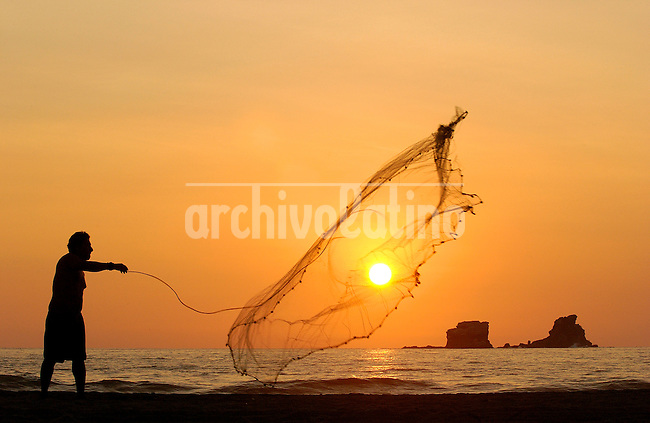 Fisherman at sunset in Ayampe in the pacific ocean in manaby province