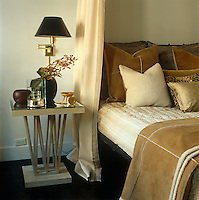 In this bedroom of a New York town house an elegant side table formed of metal struts is situated next to a bed piled high with suede, velvet and silk cushions
