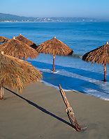 Nayarit, Mexico<br /> Thatched Pallapas on the beach in the village of Bucerias with Bahia de Banderas (Banderas Bay) and Punta de Mita in the distance