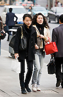 Young women walking arm in arm on Nanjing Road, central Shanghai, China