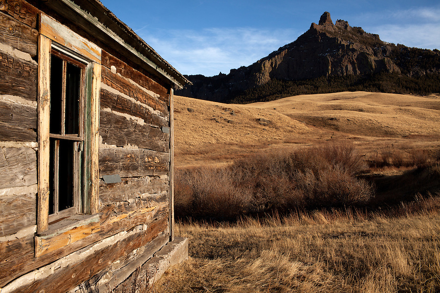 A tall rock formation juts out of the surrounding prairie as seen through the window of this abandoned log home.