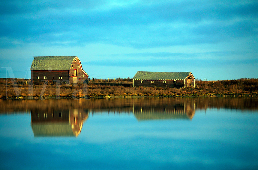 Rural country landscape of a prairie farm reflected in water. North Dakota.