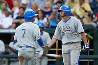 UCLA first baseman Pat Gallagher (27) greets teammate  Kevin Kramer (7) after he scored in the first inning of Game 1 at the 2013 Men's College World Series Finals against the Mississippi State Bulldogs on June 24, 2013 at TD Ameritrade Park in Omaha, Nebraska. The Bruins defeated the Bulldogs 3-1, taking a 1-0 lead in the best of 3 series. (Andrew Woolley/Four Seam Images)