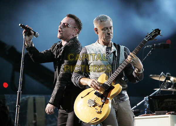 U2 - Bono (Paul David Hewson) & Adam Charles Clayton.U2's - 360° Tour, the show was being broadcast live on youtube from The Rose Bowl in Pasadena, California, USA..October 25th, 2009.stage concert live gig performance performing music half length black jacket  sunglasses shades singing profile bass.CAP/RKE/DVS.©DVS/RockinExposures/Capital Pictures