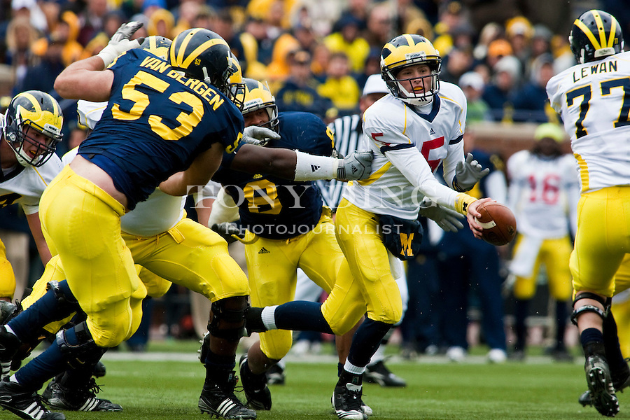 Michigan quarterback Tate Forcier (5) tries to evade defenders scrambling with the ball, during the Wolverines' spring football game, Saturday, April 17, 2010, in Ann Arbor, Mich. (AP Photo/Tony Ding)