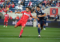 Chicago midfielder Baggio Husidic (9) prepares to shoot the ball in front of New England defender Franco Coria (2).  The Chicago Fire defeated the New England Revolution 3-2 at Toyota Park in Bridgeview, IL on Sept. 25, 2011.