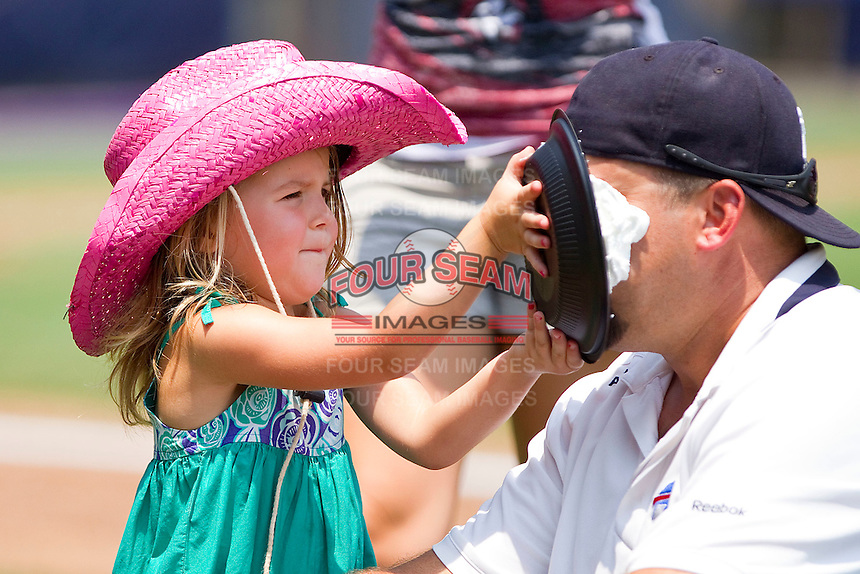 A young fan gets to hit her father with a whipped cream pie in the face between innings of the Eastern League game between the Harrisburg Senators and the Richmond Flying Squirrels at The Diamond on July 22, 2011 in Richmond, Virginia.  The Squirrels defeated the Senators 5-1.   (Brian Westerholt / Four Seam Images)