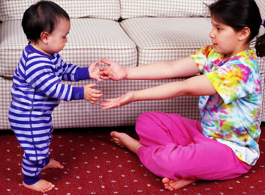 Infant is encouraged to take first step by his older sister.