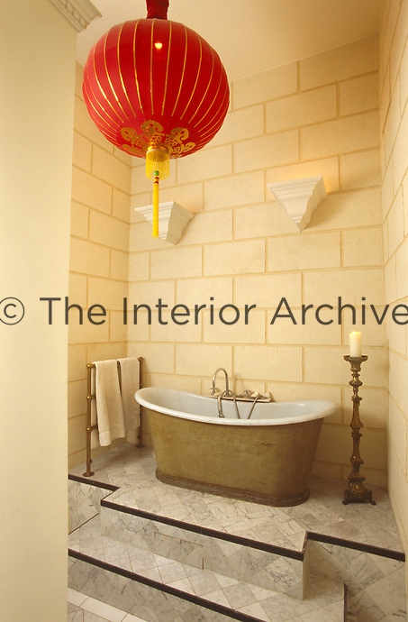 A large red Chinese lantern hangs above the roll-top bath in this bathroom with trompe l'oeil stone walls
