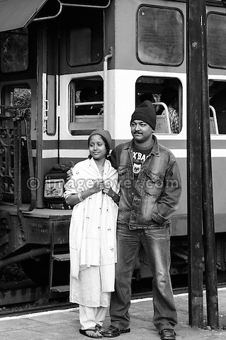 Indian couple posing in front of the Nilgiri Mountain Railway on a stop between Coonoor and Metapulayam. India, Tamil Nadu 2005. --- Info: The Nilgiri Mountain Railway (NMR) is the only rack railway in India and connects the town of Mettupalayam with the hill station of Udagamandalam (Ooty), in the Nilgiri Hills of southern India. The construction of the 46km long meter-gauge singletrack railway in Tamil Nadu State was first proposed in 1854, but due to the difficulty of the mountainous location, the work only started in 1891 and was completed in 1908. This railway, scaling an elevation of 326m to 2,203m and still in use today, represented the latest technology of the time. In July, UNESCO added the NMR as an extension to the World Heritage Site of Darjeeling Himalayan Railway.