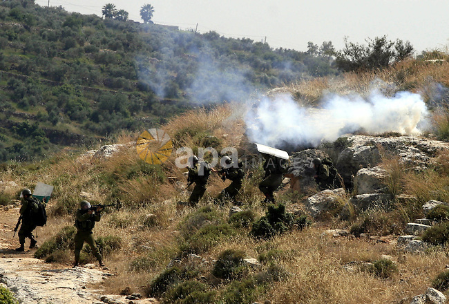 Israeli soldiers point their weapons at Palestinian stone-throwers during clashes in the West Bank village of Nabi Saleh near Ramallah, Friday, May 7, 2010. Photo by Issam Rimawi