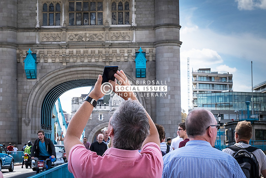 A tourist using his mobile phone to photograph Tower Bridge in London.