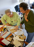 NWA Media/DAVID GOTTSCHALK - 10/6/14 - Nicole Holland, a Springdale resident, left, reviews her memorabilia with her daughter Brenda Hancock at her residence in Springdale Monday October 6, 2014. Hancock has written a book about the experience her mother had as a French Jew in the French Underground during WWII.