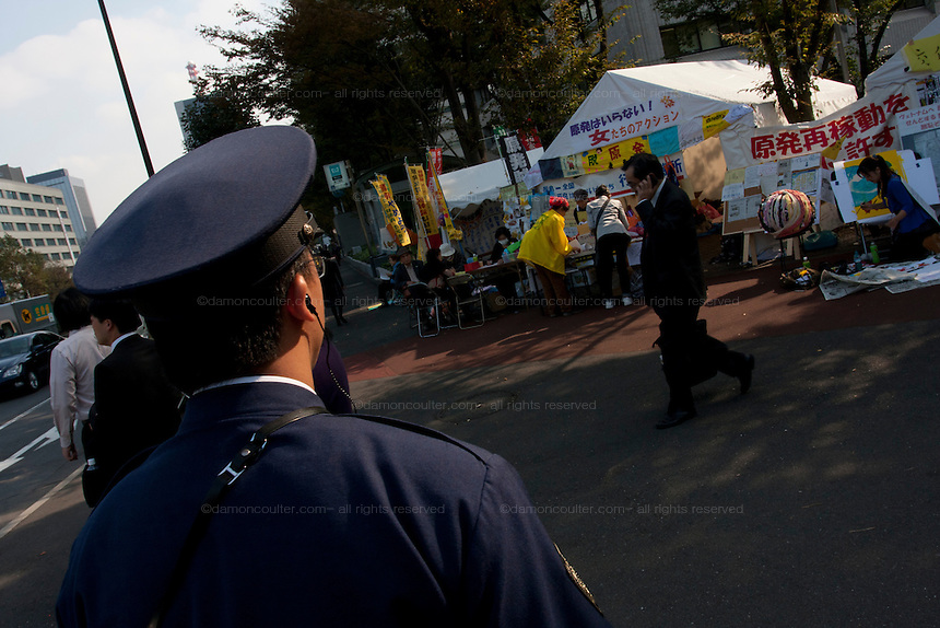 A policeman guards an Anti nuclear protest by women outside the Ministry of Economy, Trade and Industry (METI) in Tokyo Japan. Friday November 4th 2011. The protest ran from October 27th to Noverber 5th. Originally started my mothers from Fukushima protesting about nuclear contamination from October 30th to November 5th the protest welcomed women and people from all over Japan.