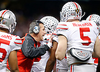 Ohio State Buckeyes head coach Urban Meyer gives his team instructions in the huddle after the first quarter of the Allstate Sugar Bowl college football playoff semifinal against the Alabama Crimson Tide at the Mercedes-Benz Superdome in New Orleans on Jan. 1, 2015. (Adam Cairns / The Columbus Dispatch)