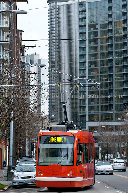 2/20/2011--Seattle, WA, USA..The South Lake Union Streetcar rolls down Westlake Avenue in the South Lake Union neighborhood, heading from downtown Seattle. Microsoft tycoon Paul Allen's brainchild of developing South Lake Union into a happening urban village is finally alive and kicking.  This former industrial no-man's-land now houses the city's best galleries, an ever increasing collection of trendy eateries, some nifty shops, and the spanking new Amazon campus. ..©2011 Stuart Isett. All rights reserved.