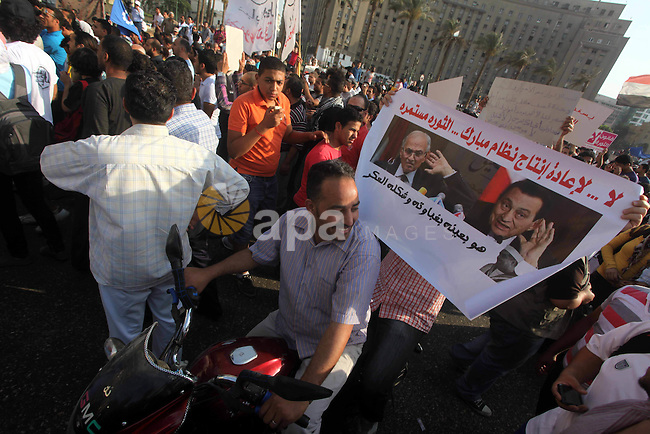 Egyptian protesters hold placards against the presidential candidate Ahmed Shafik during a demonstration in Tahrir Square decrying the result of the first round of voting in the Egyptian presidential election in Cairo, Egypt, Friday, June 1, 2012. Several hundred protesters rallied Friday in Cairo's Tahrir Square, the birthplace of the Egyptian uprising. Photo by Ashraf Amra
