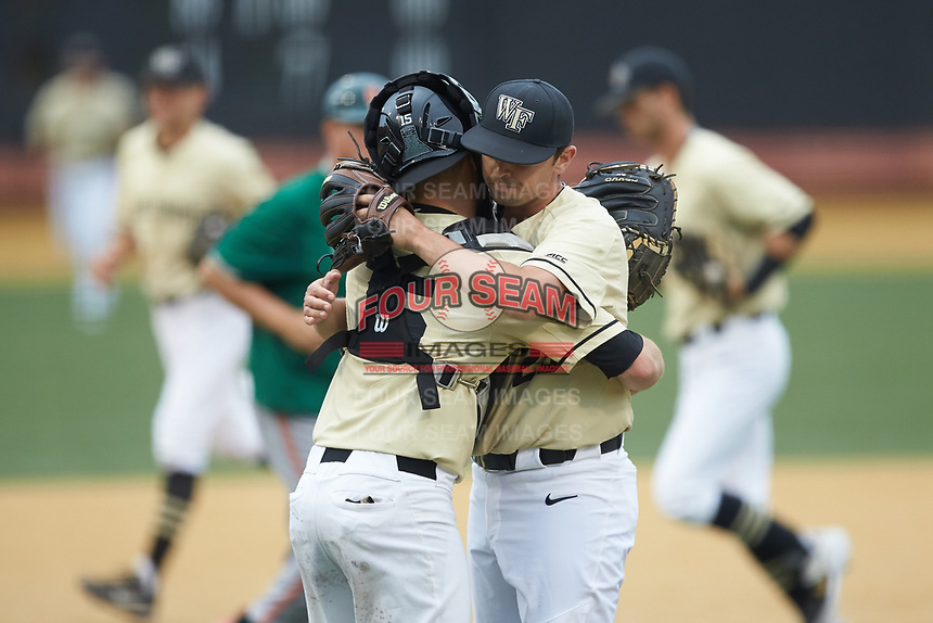 Wake Forest Demon Deacons senior pitcher Ben Casstevens (20) gets a hug from Logan Harvey (15) as he walks off the field during the game against the Miami Hurricanes at David F. Couch Ballpark on May 11, 2019 in  Winston-Salem, North Carolina. The Hurricanes defeated the Demon Deacons 8-4. (Brian Westerholt/Four Seam Images)