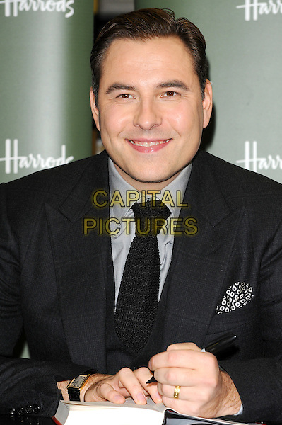 David Walliams.Signs copies of his children's novel 'Gangsta Granny' at Harrods, Knightsbridge, London, England, UK, December 3rd 2011..book half length smiling  wedding ring  photocall grey gray shirt black tie knitted .CAP/CJ.©Chris Joseph/Capital Pictures.