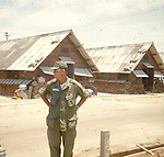 An Army soldier stands for a photo near sandbagged hooches at Red Beach. This images is from the collection of J.W. Womble of the 610th Transportation Company during the Vietnam War.