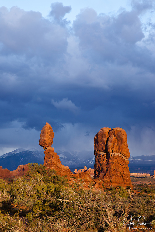 Balanced Rock in Arches National Park near Moab, Utah, USA at sunset with stormy clouds and snow on the La Sal Mountains.  Turret Arch in the backgroun.