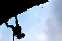 Marcelle Altshuler, 20, rappels down a 150-foot cliff at Foster Falls in Tennessee, silhouetted near a spider.