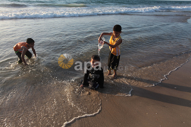 Palestinian children enjoy swimming in the sea at Gaza beach on May 2, 2014. Photo by Ashraf Amra