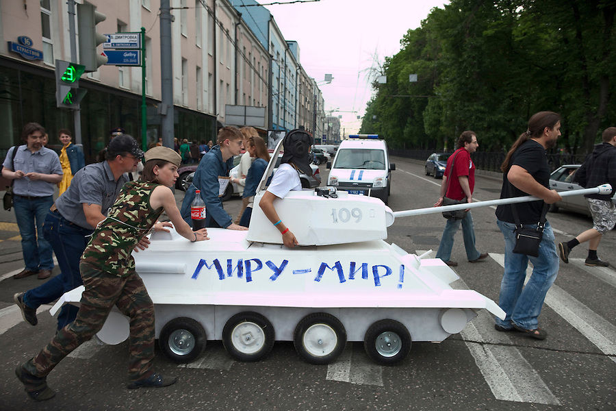 "Moscow, Russia, 19/05/2012..Artists wheel a mock tank with the slogan ""Peace to the world"" in front of a police car as several thousand artists and opposition activists demonstrate against Vladimir Putin by walking through Moscow transporting their artworks. The protest coincided with Museum Night, when Moscow's museums are open until midnight with special exhibitions and performances."