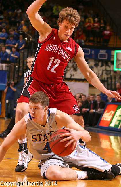 BROOKINGS, SD - MARCH 1:  Jake Bittle #4 from South Dakota State University hangs on to the ball while on the floor and being guarded by Brandon Bos #12 from the University of South Dakota in the second half or their game Saturday afternoon at Frost Arena in Brookings. (Photo by Dave Eggen/Inertia)