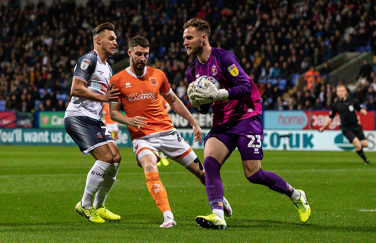 Bolton Wanderers' Dennis Politic (left) competing with Blackpool's Jak Alnwick (right) and James Husband <br /> <br /> Photographer Andrew Kearns/CameraSport<br /> <br /> The EFL Sky Bet League One - Bolton Wanderers v Blackpool - Monday 7th October 2019 - University of Bolton Stadium - Bolton<br /> <br /> World Copyright © 2019 CameraSport. All rights reserved. 43 Linden Ave. Countesthorpe. Leicester. England. LE8 5PG - Tel: +44 (0) 116 277 4147 - admin@camerasport.com - www.camerasport.com