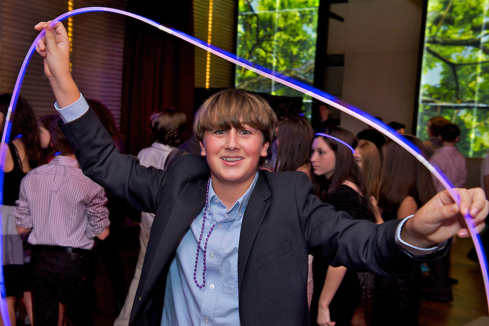 Boy holding a glow tube on the dance floor.