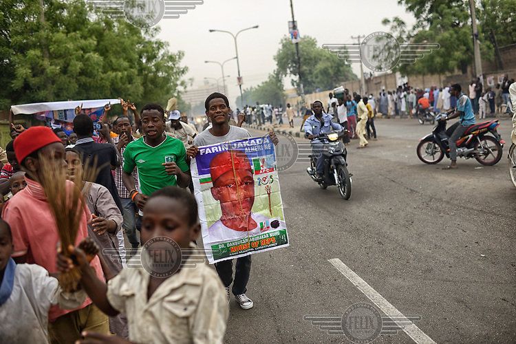 A young man carries a poster featuring a local APC (All Progressives Congress Party) candidate, Dr. Danburam Abubakar Nuhu, as jubilant youths come onto the streets of Kano to celebrate the victory of Muhammadu Buhari, leader of the APC, in the 2015 Nigerian Presidential elections.