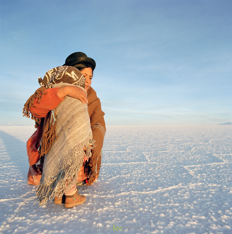 Profile portrait of young boy and his mother in traditional dress on Salar de Uyuni salt flats, Bolivia. The Salar de Uyuni are the worlds largest salt flats.