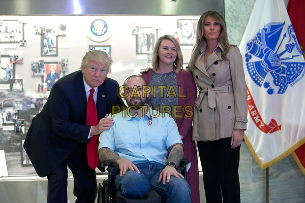 US President Donald J. Trump (L), with First Lady Melania Trump (R), talks with Sergeant First Class Alvaro Barrientos (2-L), with his wife Tammy Barrientos (2-R), after awarding the Purple Heart to him during a visit to Walter Reed National Military Medical Center in Bethesda, Maryland, USA, 22 April 2017. Sergeant First Class Alvaro Barrientos was recently injured in Afghanistan while deployed and for the wounds he sustained, he is receiving the Purple Heart.<br /> CAP/MPI/RS<br /> &copy;RS/MPI/Capital Pictures