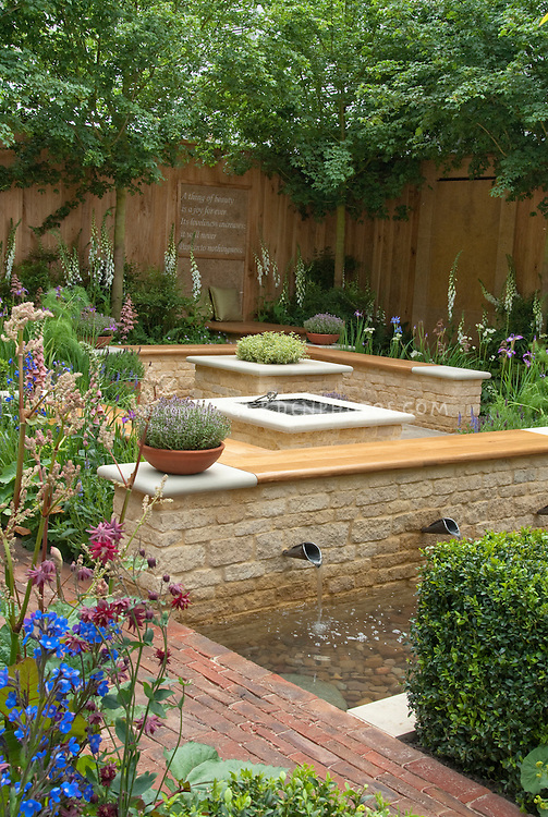 Keats A thing of beauty is a joy forever motto on garden fence wall, with bench, cushions, place to relax, foxglove white flowers, tree, privacy in backyard, water garden and waterfalls, brick path, privacy, sense of enclosure for an outdoor room in the backyard