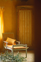 A cane-backed chaise-longue in a bedroom beside a hand-painted corner cupboard